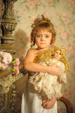 Little girl with a doll in hands Stock Photo