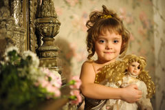 Little girl with a doll in hands. Stock Photo