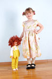 Little girl with doll at wall Royalty Free Stock Image