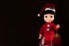 Little girl doll , wearing Santa's hat. In black background Stock Photos