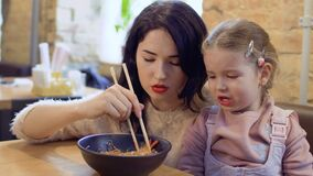 Little girl don`t want to eat a korean noodles. Young beautiful mother feeds her little daughter with korean noodles. Little girl don`t want to eat a noodles and stock video