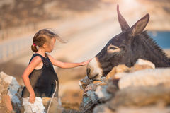 Little girl with donkey on the island of Mykonos Royalty Free Stock Photography