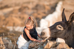 Little girl with donkey on the island of Mykonos Royalty Free Stock Image