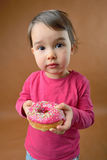 Little girl with donut stock images