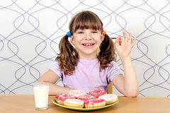 Little girl with donuts and ok hand sign Royalty Free Stock Photography