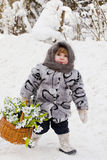 Little girl in a down scarf, a fur coat and valenoks bears a bi Royalty Free Stock Photography