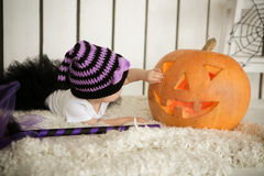 Little girl with Down Syndrome finger touches the eyes of a pumpkin on Halloween Stock Photos