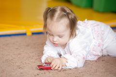 Little Girl with Down syndrome playing car Stock Photo