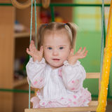 Little girl with Down syndrome playing hide and seek. Girl with Down syndrome playing hide and seek Royalty Free Stock Photography