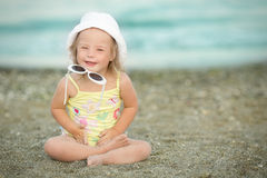 Little girl with Down syndrome playing  sunglasses on the beach Stock Photography