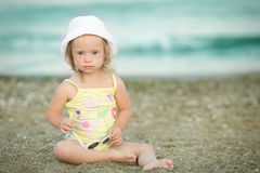 Little girl with  Down syndrome playing sunglasses on the beach Royalty Free Stock Image