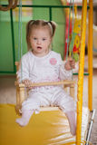 Little Girl with Down syndrome is riding on a swing. Girl with Down syndrome is riding on a swing Royalty Free Stock Photos