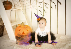 Little girl with Down Syndrome sitting with a broom near the big pumpkin Stock Photo