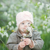 Little girl with Down syndrome smelling flowers. Little girl  with Down syndrome smelling flowers Stock Image