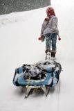 Little girl dragging big sled Stock Photos