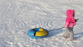 Little girl drags bright snowtube on snow stock video