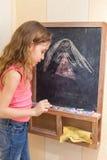 Little girl draw on blackboard Stock Images