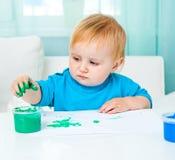 Little girl draw finger paints Stock Image