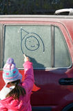 Little girl draw a happy face on a frosted car window Royalty Free Stock Image