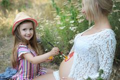 Little girl draw a house on her pregnant mother stomach. Happy childhood royalty free stock photos