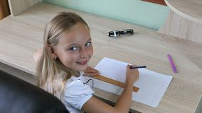 Little girl draw line by pencil with ruler in notebook. Back to school concept. Young girl sitting by table indoors Stock Photo