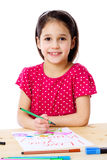 Little girl draw for mum. Smiling little girl at the table draw with crayons for mum, isolated on white Stock Photo