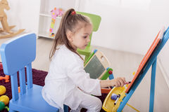 Little girl draw in room Royalty Free Stock Image