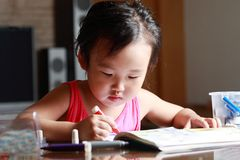 Little girl drawing. Cute little girl drawing.at home stock image