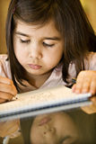 Little Girl Drawing. Girl drawing and shows reflection of her face on the glass table Stock Image