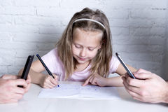Little girl drawing alone while her parents all time networking mobile phone ignoring her daughter. Sweet cute little girl drawing alone while her parents spend royalty free stock images