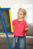 Little girl drawing on board Stock Photography