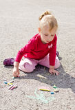 Little girl drawing with chalk Stock Images