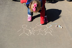 Little girl drawing with chalk on asphalt Stock Image