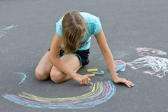 Little girl drawing a chalk on the asphalt Royalty Free Stock Images