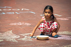 Little Girl drawing with Chalk Royalty Free Stock Photos