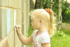 Little girl drawing with chalk on the wall Royalty Free Stock Image