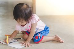 Little girl drawing with color pencil on paper while sittin. G at home Royalty Free Stock Image