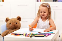 Little girl drawing with color pencils - sitting at the table Royalty Free Stock Photography