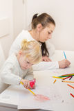 Little girl drawing with colorful crayons Royalty Free Stock Image