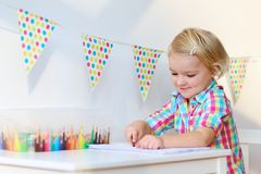 Little girl drawing with colorful pencils Royalty Free Stock Images