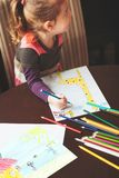 Little girl drawing a colorful pictures of giraffe and playing c. Hildren using pencil crayons sitting at table indoors. Shot from above Stock Photo