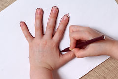 Little girl is drawing contour of the hand. Closeup Stock Images