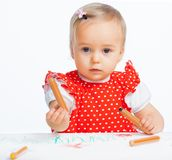 Little girl drawing with crayons Stock Images