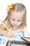 Little girl drawing at the desk Stock Images