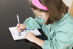 Little girl drawing a dinosaur in a notebook Royalty Free Stock Photo