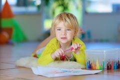 Little girl drawing on floor indoors. Happy little child, adorable blonde toddler girl lying comfortable on tiles floor on warm lambskin drawing on paper with Stock Photos