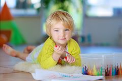 Little girl drawing on floor indoors. Happy little child, adorable blonde toddler girl lying comfortable on tiles floor on warm lambskin drawing on paper with Royalty Free Stock Image