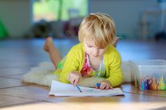 Little girl drawing on floor indoors Royalty Free Stock Photos