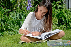Little Girl Drawing in the Garden Royalty Free Stock Photography