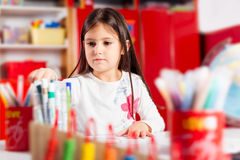 Little girl drawing on her book and having fun at play table Stock Image